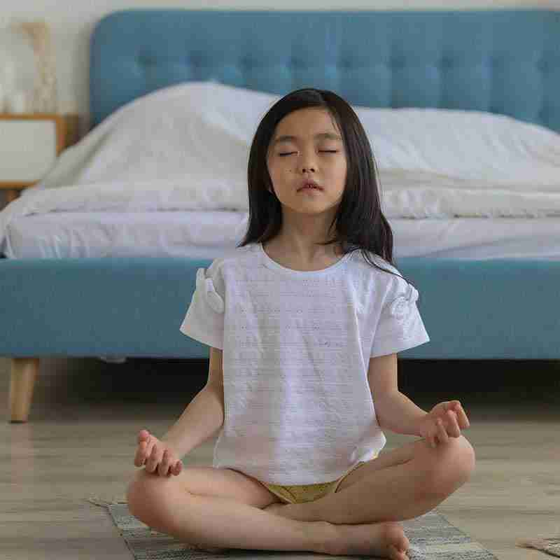 asian child practicing mindful meditation